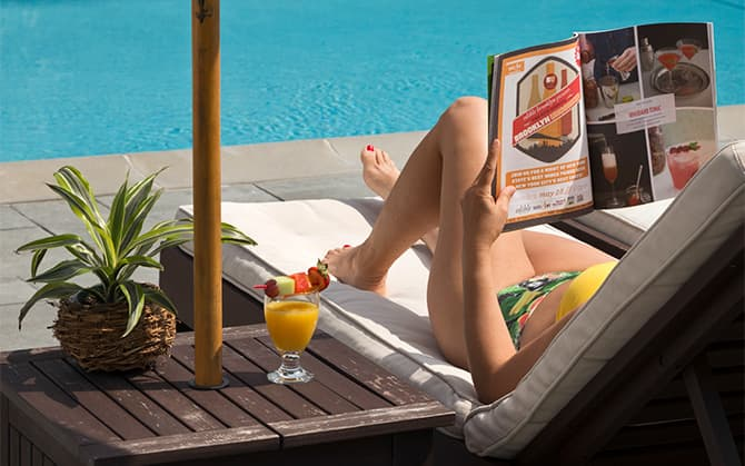 Woman lying by the pool reading a magazine.